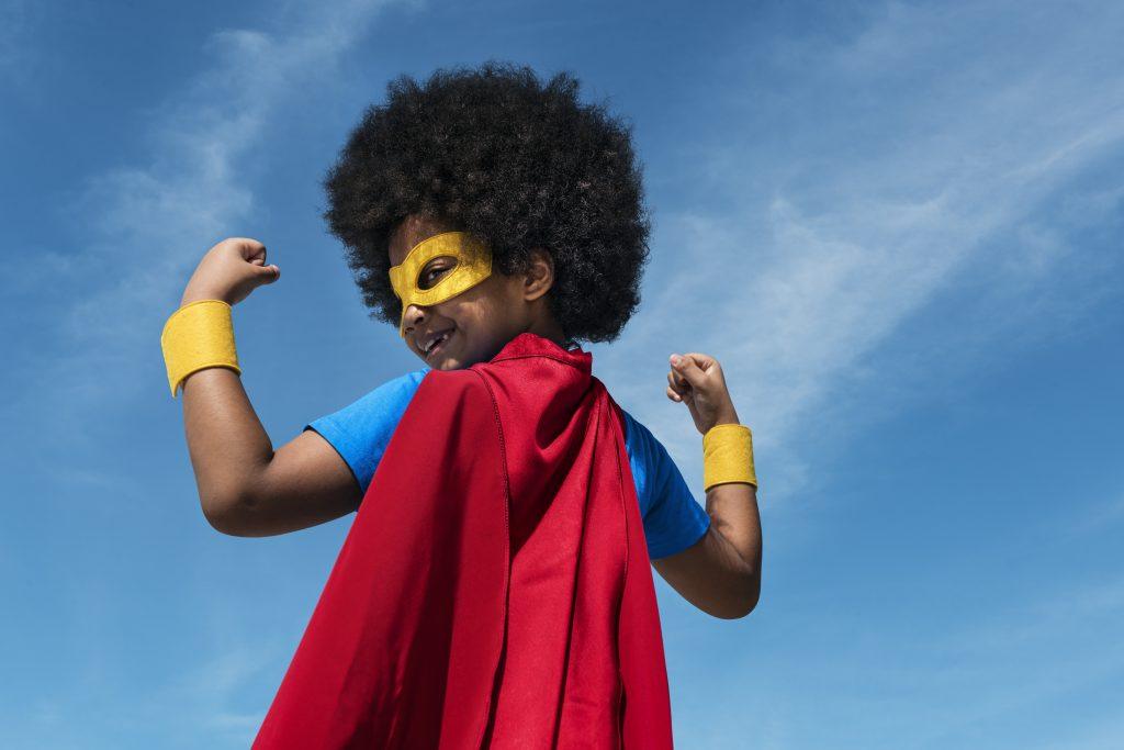 A little boy is dressed as a superhero.